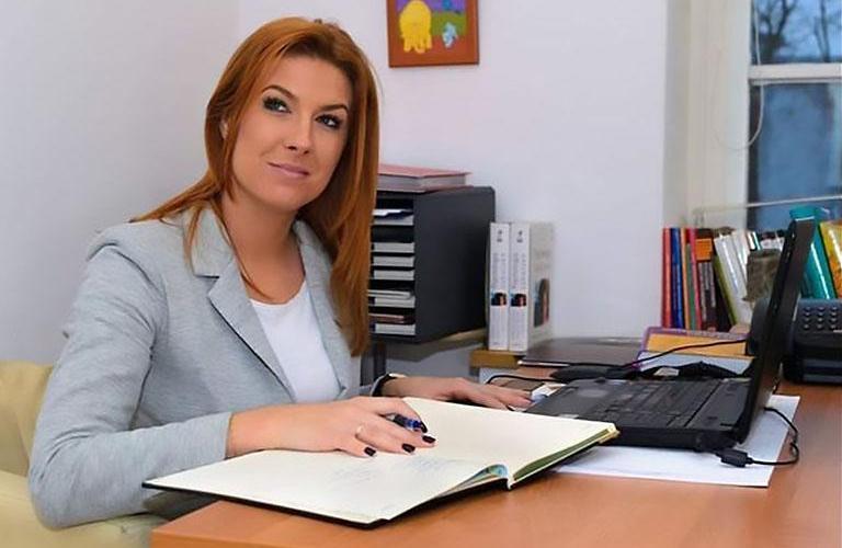 kobieta siedząca zabiurkiem zdokumentami